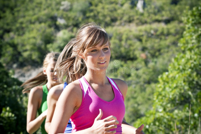 Female Jogger running outdoors. With a group of friends stock images