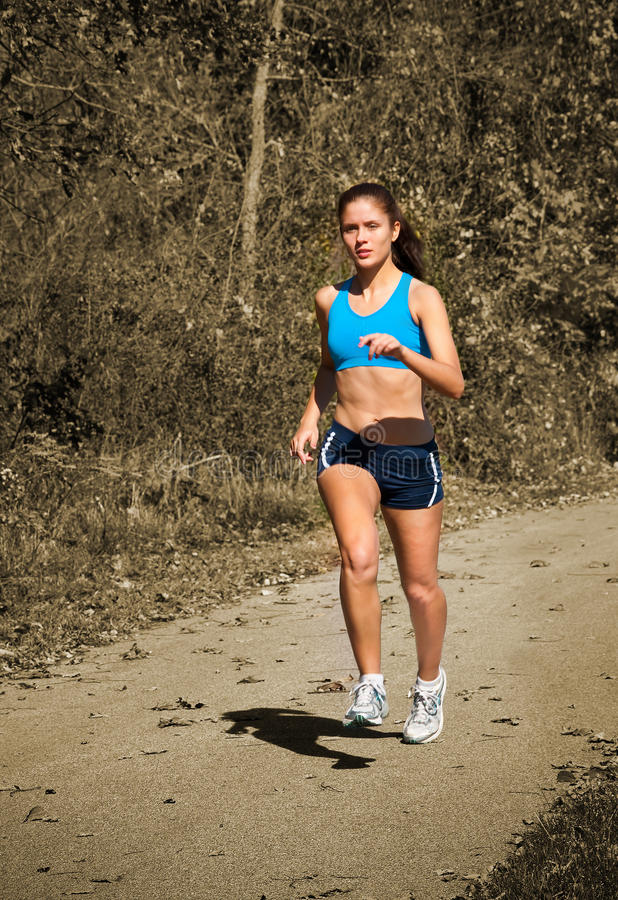 Female Jogger Running in Park. Female jogger running outside in the park royalty free stock images
