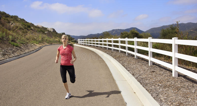 Female Jogger running on the road. An attractive female jogger running outdoors on a sunny morning along a road royalty free stock photo