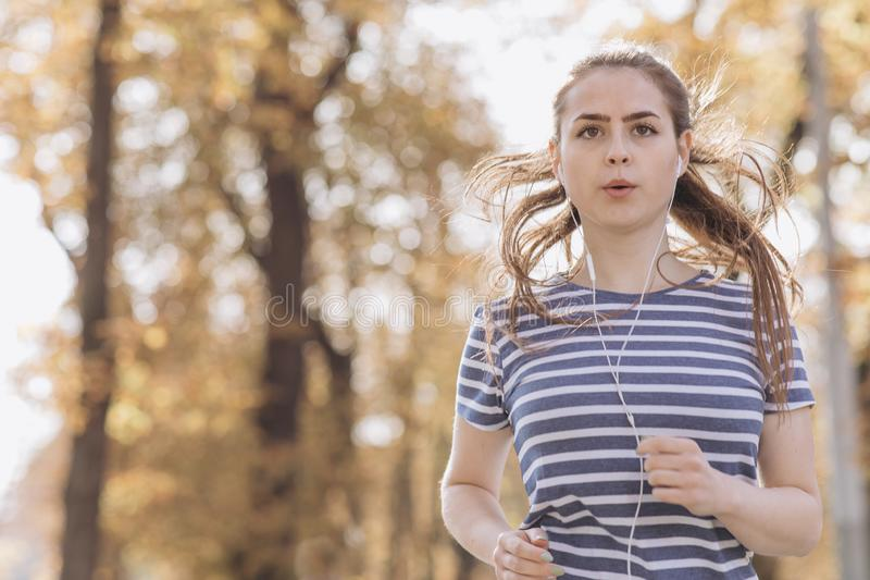 Female jogger running on road and street in park with trees. Woman in jogging trail in the morning. Runner doing outdoor royalty free stock photos