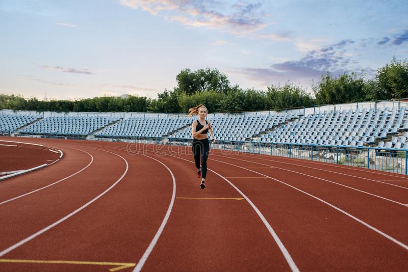 Female jogger running, training on stadium. Female jogger in sportswear running, training on stadium. Woman doing stretching exercise before jogging on outdoor stock photography