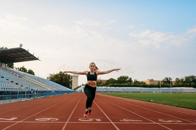 Female jogger in sportswear crosses finish line. Female jogger in sportswear crosses the finish line, training on stadium. Woman doing stretching exercise before royalty free stock image