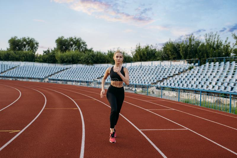 Female jogger running, training on stadium. Female jogger in sportswear running, training on stadium. Woman doing stretching exercise before jogging on outdoor stock photos