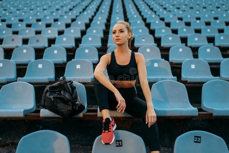 Female jogger in sportswear sitting on tribune. Training on stadium. Woman doing stretching exercise before running on outdoor arena royalty free stock photo