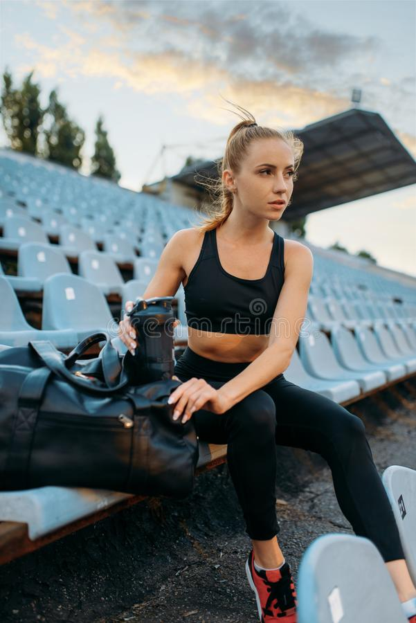 Female jogger in sportswear sitting on tribune. Training on stadium. Woman doing stretching exercise before running on outdoor arena royalty free stock images