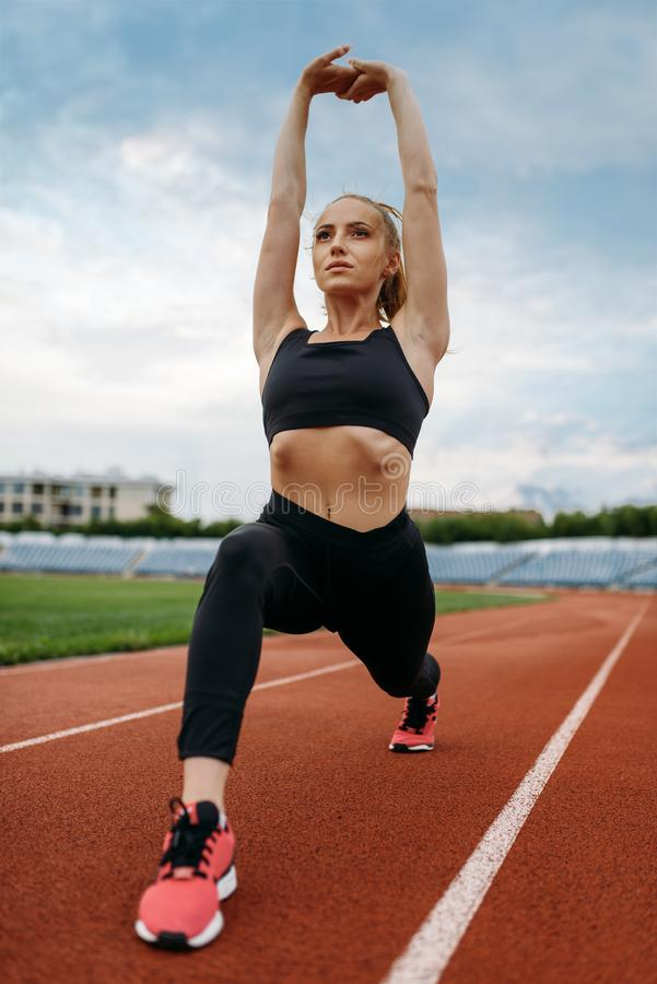 Female jogger in sportswear, training on stadium. Woman doing stretching exercise before running on outdoor arena stock photography