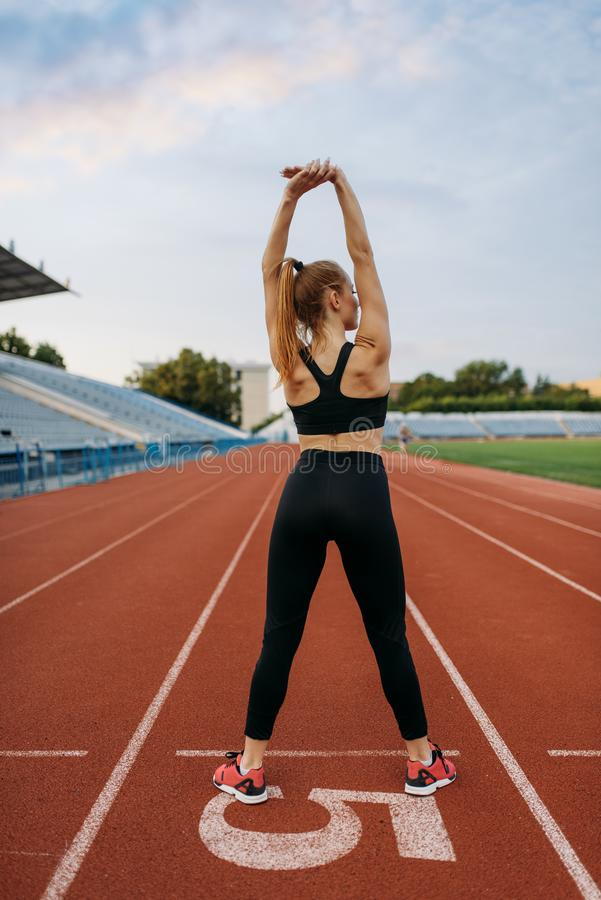 Female jogger in sportswear, training on stadium. Woman doing stretching exercise before running on outdoor arena royalty free stock photography