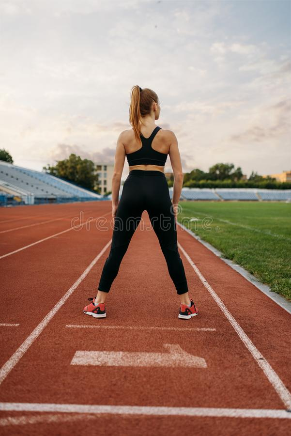 Female jogger in sportswear, training on stadium. Woman doing stretching exercise before running on outdoor arena royalty free stock image