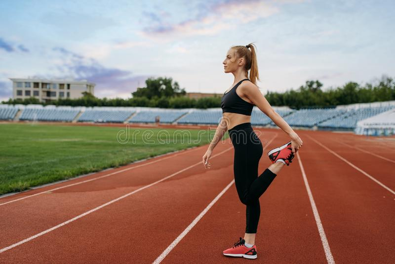 Female jogger in sportswear, workout on stadium. Woman doing stretching exercise before running on outdoor arena stock photos