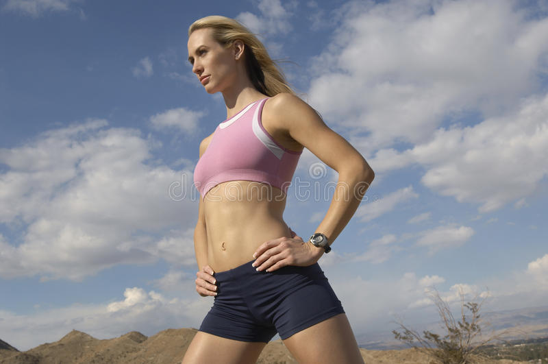 Female Jogger Standing With Hands On Hips Outdoors. Beautiful young female jogger standing with hand on hip against cloudy sky royalty free stock image