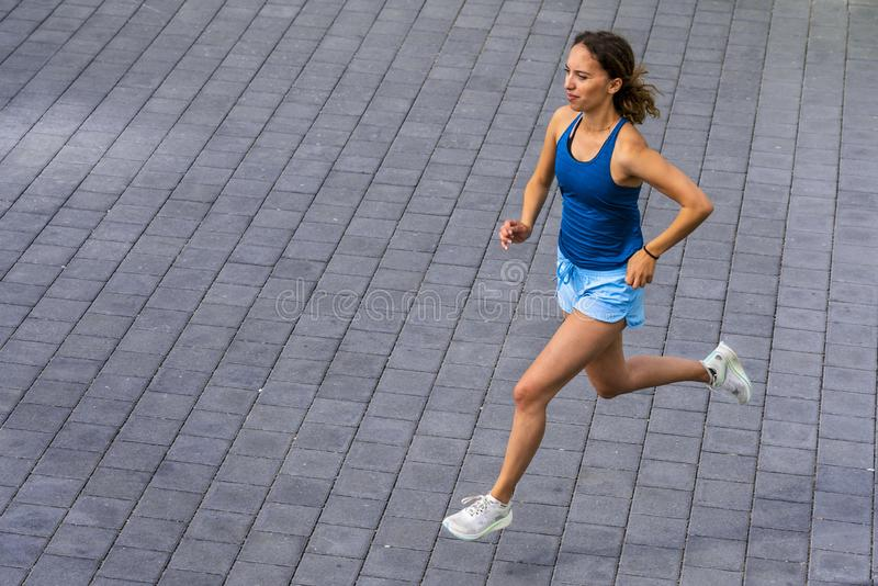 Female jogger on a street. Female jogger in a view from straight above, shot in daylight in spring stock photos