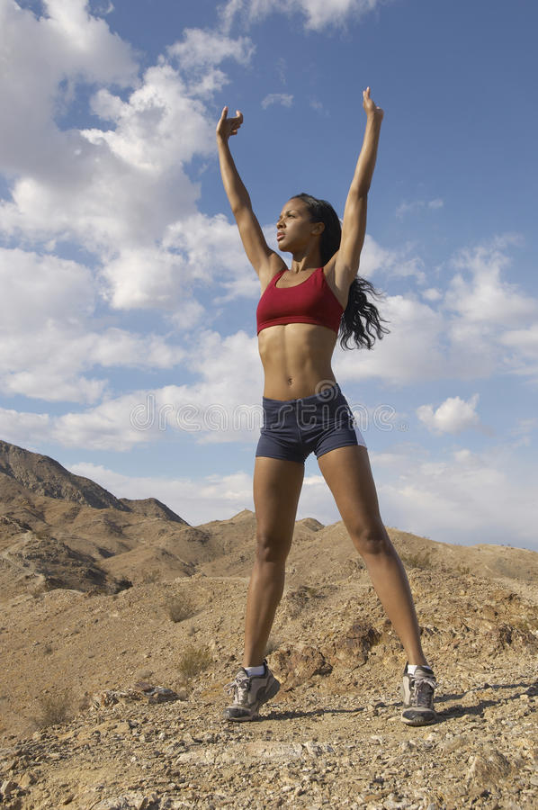 Female Jogger Stretching Her Arms Outdoors. Mixed race female jogger stretching her arms in mountains stock photos