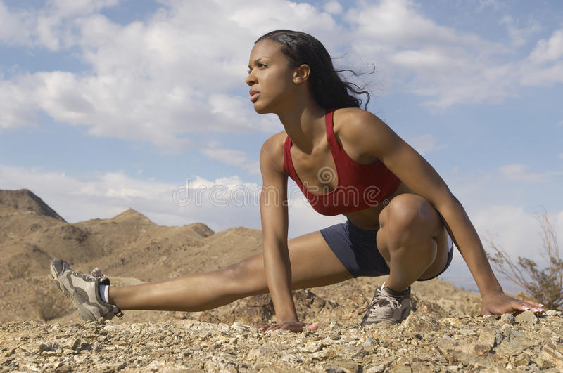 Female Jogger Stretching In Mountains. Mixed race female jogger stretching in mountains against cloudy sky royalty free stock photography