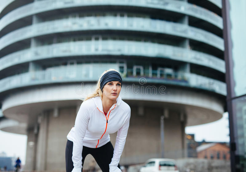 Female jogger taking a break. Young woman on sports exercising workout outdoor. Female fitness athlete working out for healthy lifestyle. Female jogger taking a stock photography