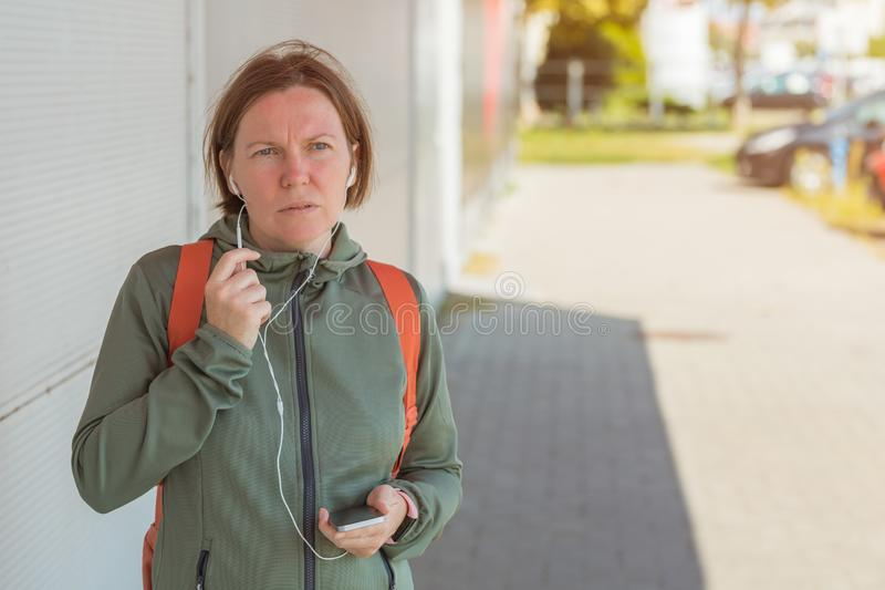 Female jogger talking on mobile phone handsfree royalty free stock image