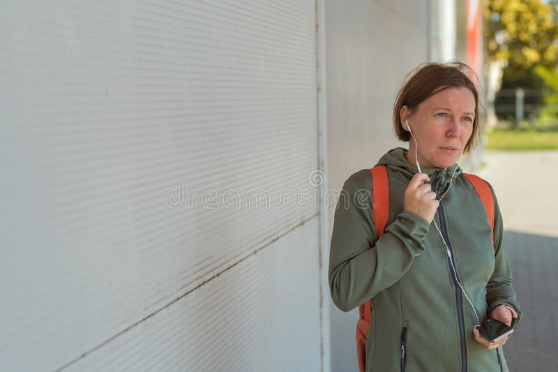 Female jogger talking on mobile phone handsfree. While brisk walking the street stock photos