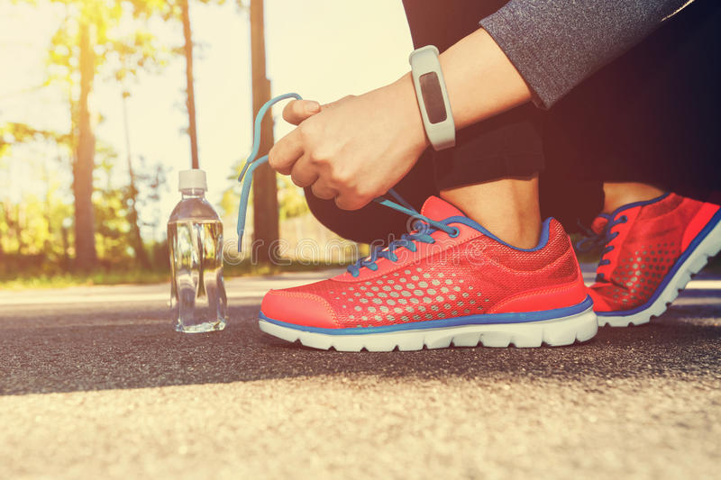 Female jogger tying her running shoes. Outside royalty free stock photo