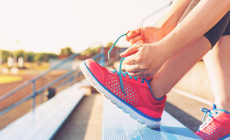 Female jogger tying her shoes on the bleachers. Female runner lacing her sneakers on in the bleachers of a stadium royalty free stock images