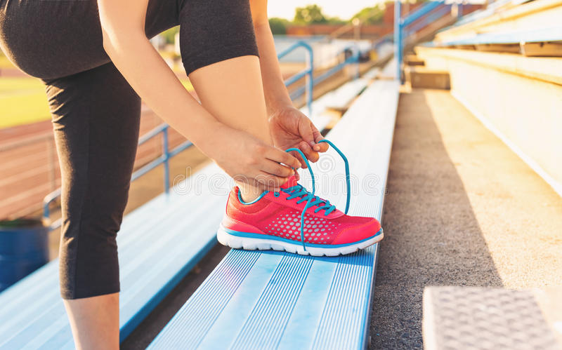Female jogger tying her shoes on the bleachers. Female runner lacing her sneakers on in the bleachers of a stadium stock photo