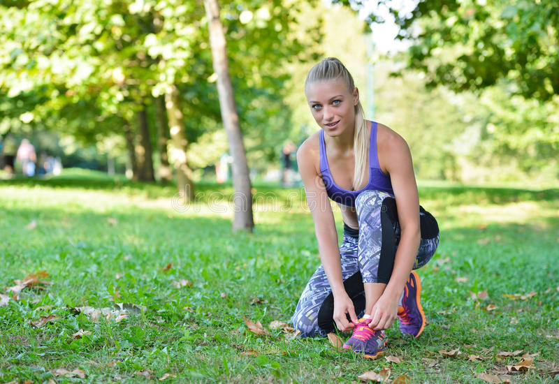 Female jogger tying laces on her shoes outside.  stock photography
