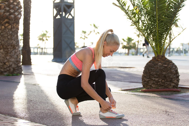 Female jogger tying shoelaces on her running shoes during fitness training in urban setting. Portrait of smiling beautiful female jogger tying shoelaces on her royalty free stock images