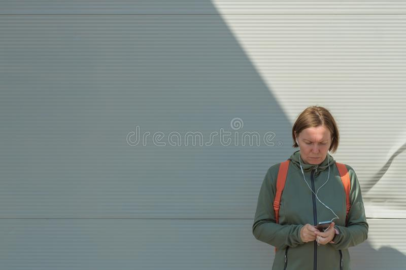 Female jogger using smartphone for text messaging on street. While standing next to the wall in urban surrounding stock photos