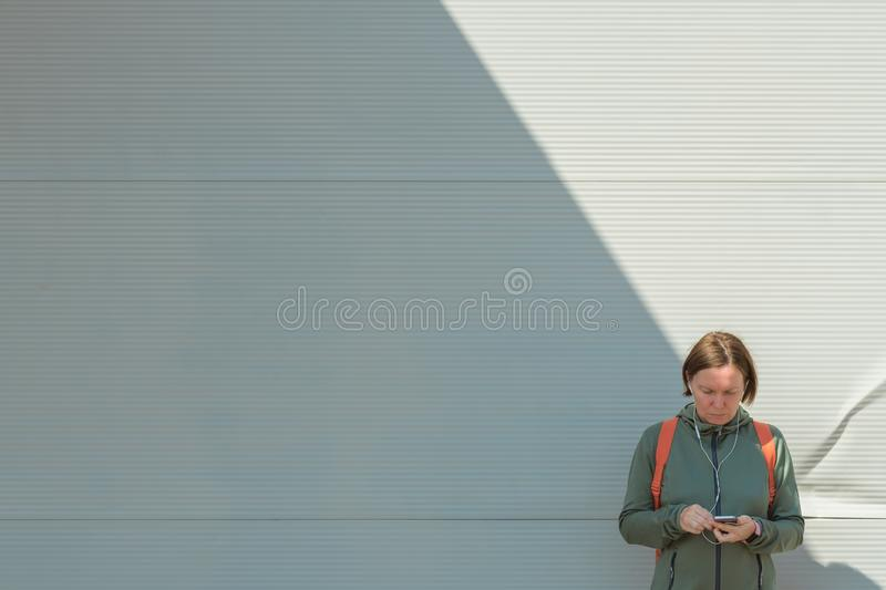 Female jogger using smartphone for text messaging on street. While standing next to the wall in urban surrounding royalty free stock photography