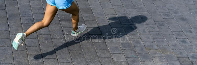 Female jogger on a street. Female jogger in a view from straight above, shot in daylight in spring royalty free stock photo