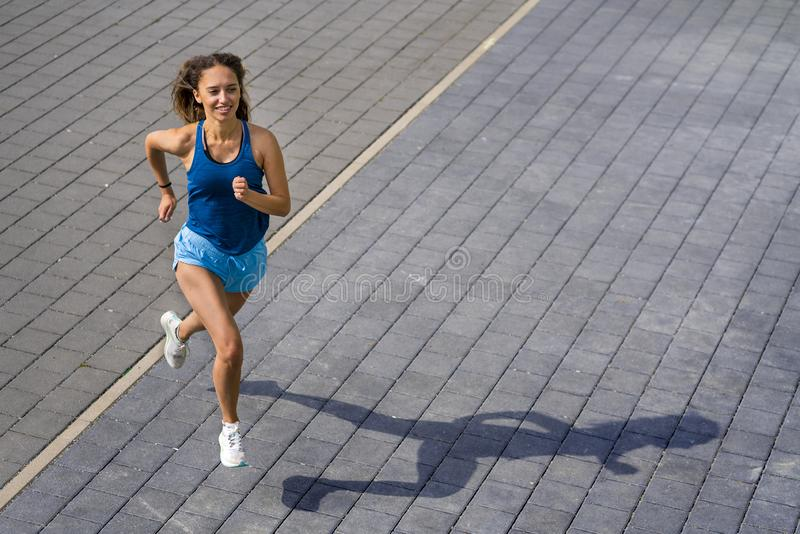 Female jogger on a street. Female jogger in a view from straight above, shot in daylight in spring stock images