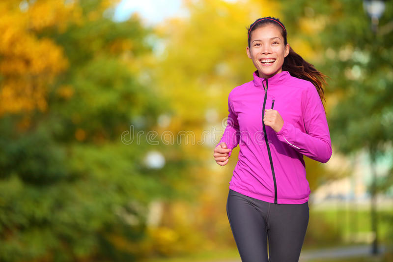 Female jogger - young woman jogging in the park. Female jogger. Fit young Asian woman jogging in park smiling happy running and enjoying a healthy outdoor royalty free stock image