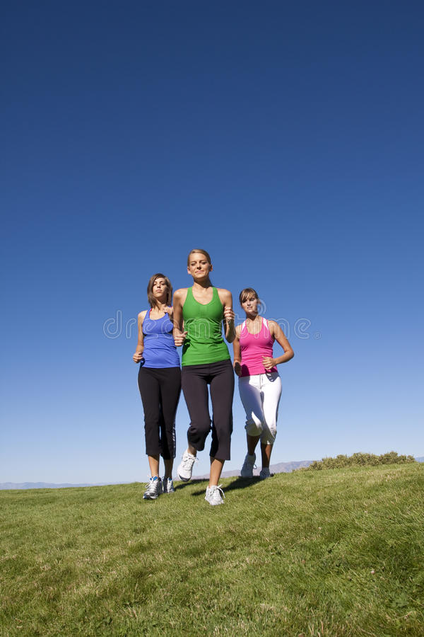 Female joggers. A group of female joggers running outdoors. Lots of Copy space stock image