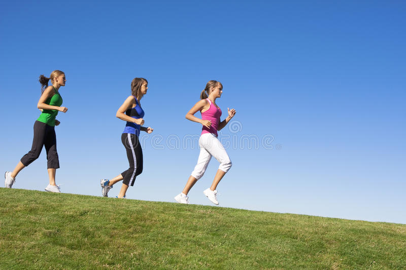 Female Joggers on the horizon. A group of female joggers running along the grassy horizon down the hill stock photos