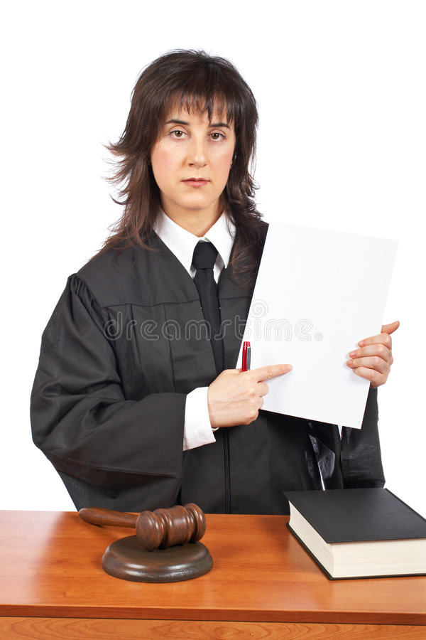 Female judge points to blank court order. A female judge points to blank court order, over a white background. Shallow depth of field royalty free stock image
