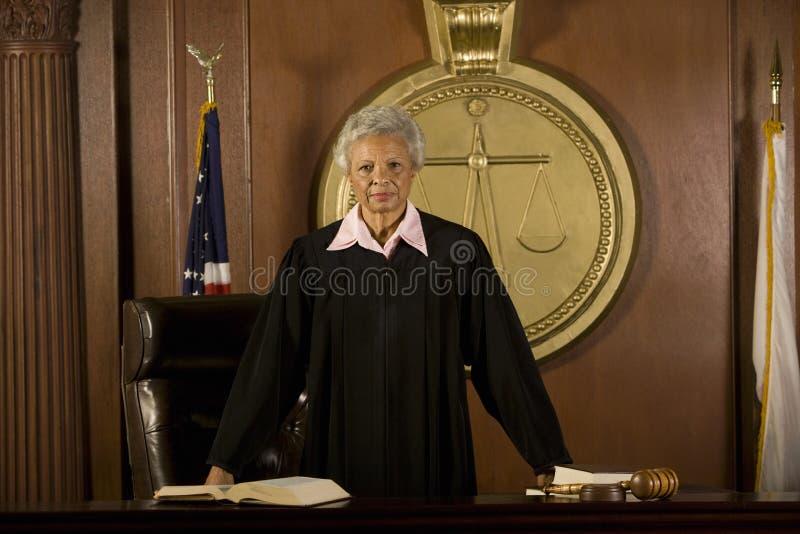 Female Judge Standing In Court Room. Portrait of confident senior female judge standing in court room stock images
