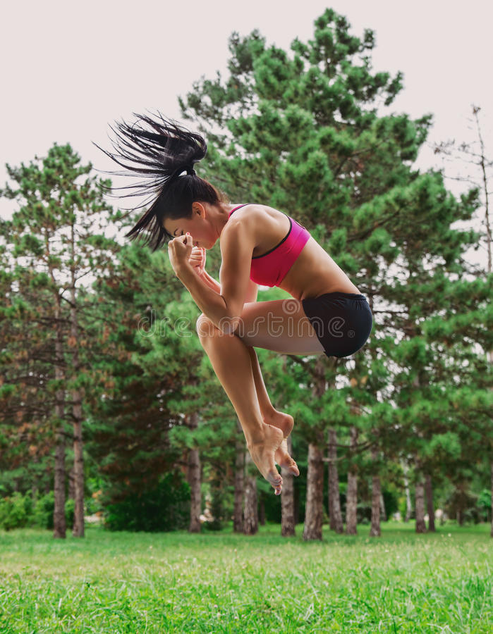 Female jumping outside in the park royalty free stock photo
