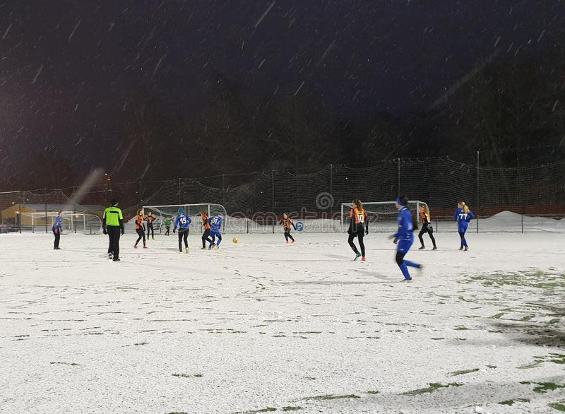 Female junior football match in winter on snow covered field - Helsinki, Finland stock photography