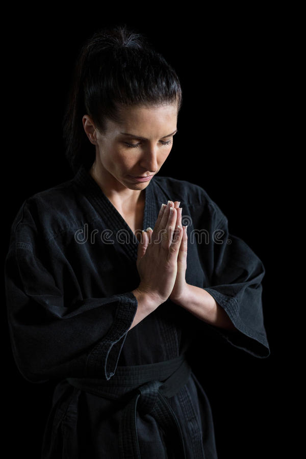 Female karate player in prayer pose. Against black background royalty free stock images