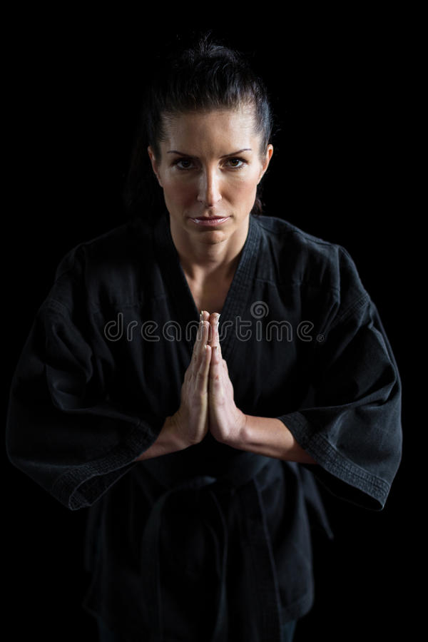 Female karate player in prayer pose. Portrait of female karate player in prayer pose against black background royalty free stock images
