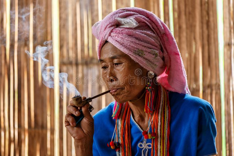 Female karen hill tribe is smoking tobacco pipe traditional in the cottage of northern Thailand at Mae Klang Luang. Mae Chaem, Chiang Mai Province stock photography