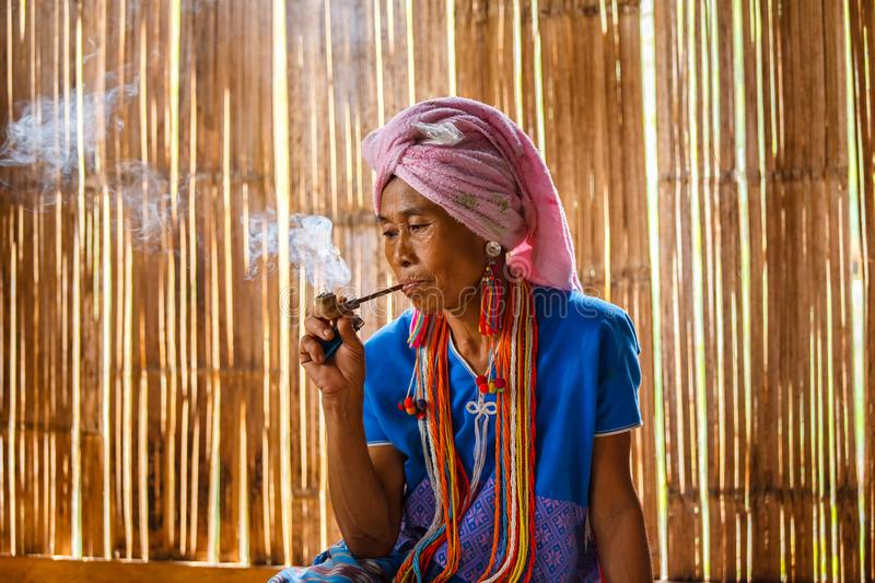 Female karen hill tribe is smoking tobacco pipe traditional in the cottage of northern Thailand at Mae Klang Luang royalty free stock photos