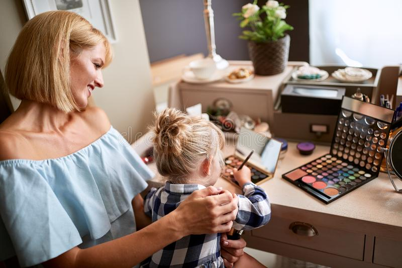 Female kid is amusing with make up royalty free stock photo