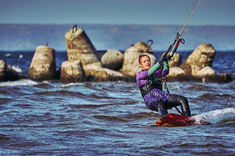 A female kiter slides on the surface of the water. royalty free stock photography
