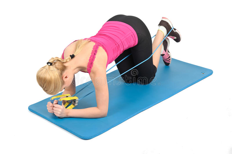 Female kneeling blaster. Young blond girl doing kneeling blaster exercise using rubber resistance band. position 1 of 2 stock image