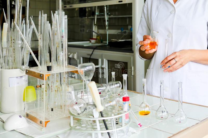 A female laboratory assistant, a doctor, a chemist, works with flasks, test tubes, makes solutions, medicines, mixes ingredients. A female laboratory assistant royalty free stock image
