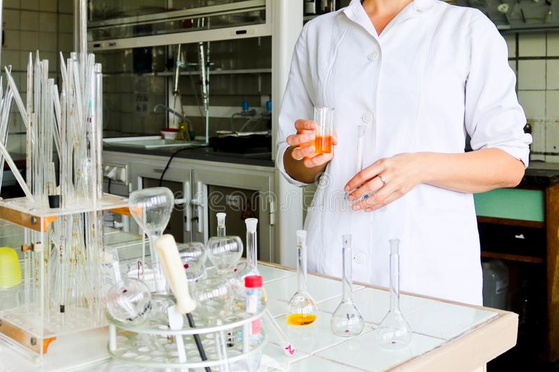 A female laboratory assistant, a doctor, a chemist, works with flasks, test tubes, makes solutions, medicines, mixes ingredients. A female laboratory assistant royalty free stock photography