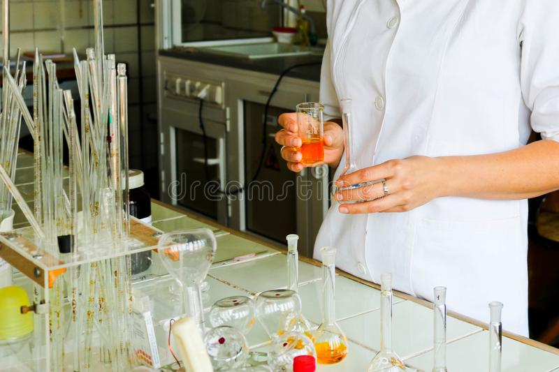 A female laboratory assistant, a doctor, a chemist, works with flasks, test tubes, makes solutions, medicines, mixes ingredients. A female laboratory assistant stock image