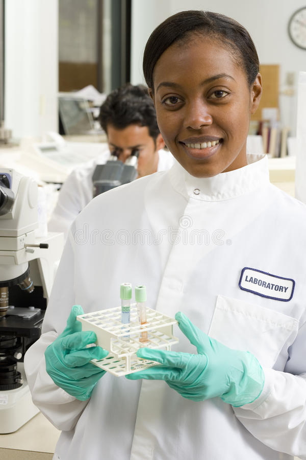 Female laboratory technician with test tubes, smiling, portrait royalty free stock photography