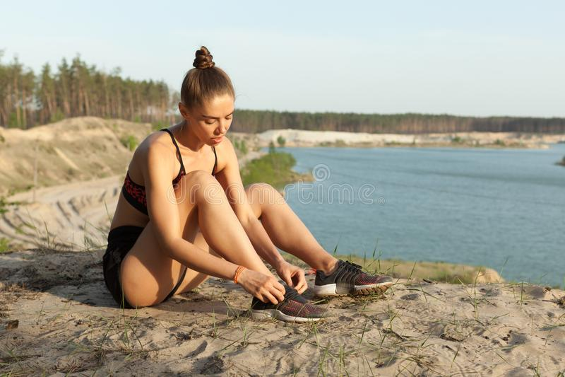 Female lacing sport shoes. Fitness woman tying shoe lace before running outdoors, workout wellness concept. stock images