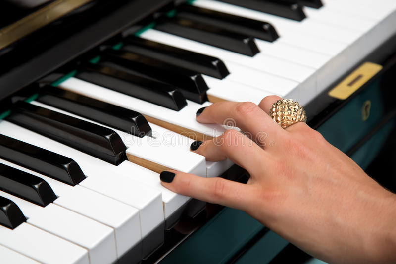Female lady fingers on the piano keys stock image