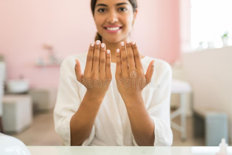 There`s Nothing Great Like Having Your Hands Pampered In Spa. Female Latin customer showing her polished fingernails at beauty salon royalty free stock photo